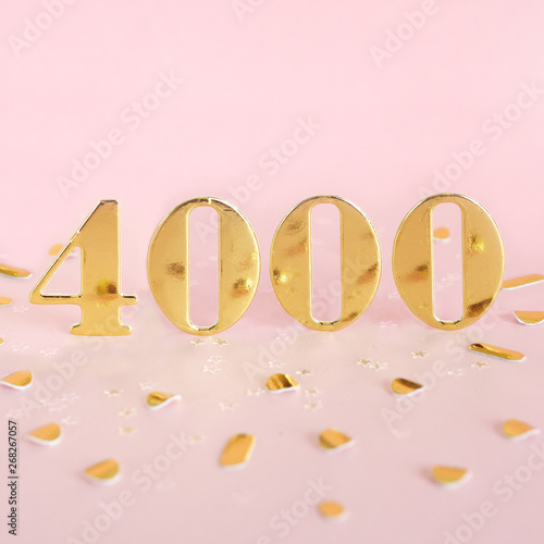 The number 4000 in golden numbers on a pink background and golden confetti Tablou Canvas