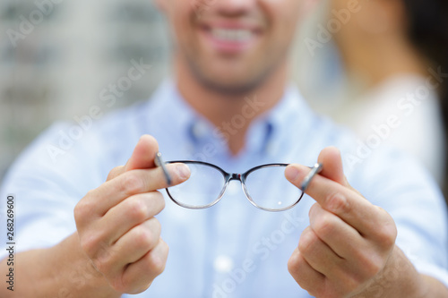 Fotomural close up view of spectacles held by male optician