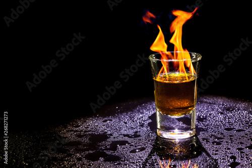 Foto auf Leinwand Alkohol Hot alcoholic cocktail burning in shot glass on black background.