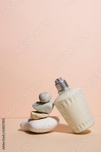 Fotografie, Obraz  Body lotion with pile of spa stones