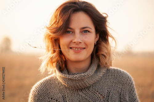 Photo  Portrait joyful young woman brunette in brown knit sweater made of natural wool and jeans having fun, smile and enjoy day on field
