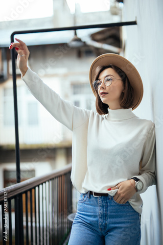 Photo  Portrait of a beautiful woman wearing in hat on the balcony and wave with hands