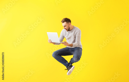Fotografia  Jumping young man with laptop on color background