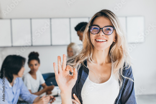 Obraz Close-up portrait of pretty female manager from sales department. Indoor photo of smiling girl working in office with discussing people on background. - fototapety do salonu