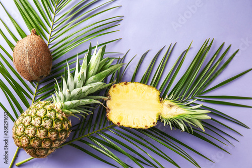 Foto auf Gartenposter Palms Ripe pineapples, coconut and palm leaves on color background