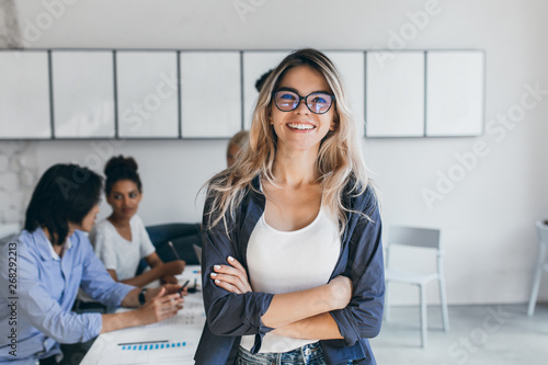 Fotomural Pleased female secretary in trendy glasses posing in office after meeting with colleagues