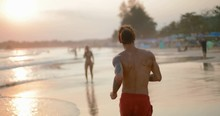 Young Man With Sporty Body Running Along The Ocean At Sunset.  Tracking Shot. Real Time. Shot On Canon 1DX Mark2 4K Camera
