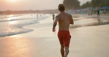 Young Man With Sporty Body Running Along The Ocean At Sunset. Tracking Shot. In Slow Motion. Shot On Canon 1DX Mark2 4K Camera