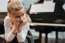 Portrait Of Disappointed Little Girl Trying To Play Piano