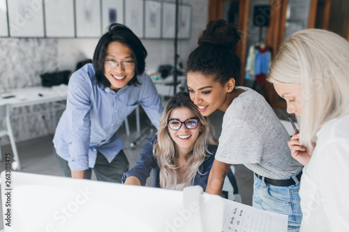 Fotografía  Long-haired blonde secretary in glasses laughing while looking at computer with asian programmer and african girl
