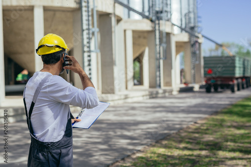 worker controlling grain loading on agricultural farm Canvas Print