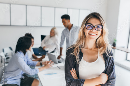 Fotografía  Blonde female executive posing with smile and arms crossed during brainstorm with managers