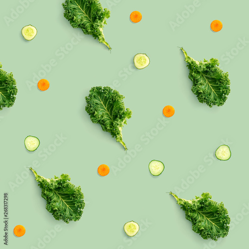 Cadres-photo bureau Cuisine Creative pattern made of kale, cucumber and carrot on green background. Flat lay. Food concept.