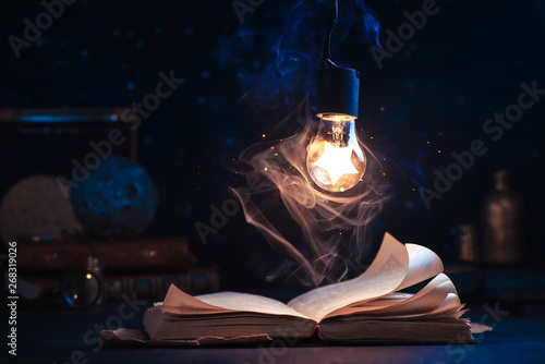 Photo  An open book with lighting by a star inside a lightbulb
