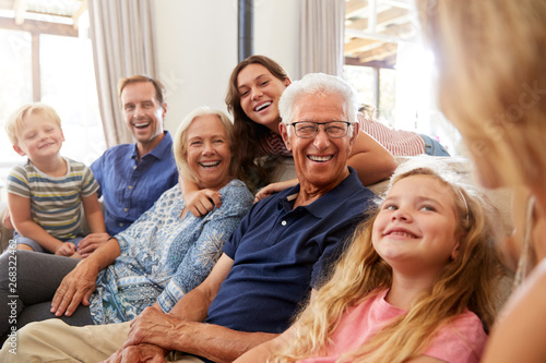 Photographie  Multi-Generation Family Sitting On Sofa At Home Relaxing And Chatting
