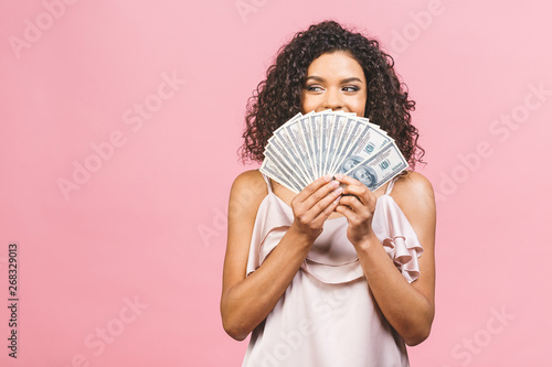 Fototapeta Rich girl! Money winner! Surprised beautiful african american woman in dress holding money and looking at the camera isolated against pink background. obraz