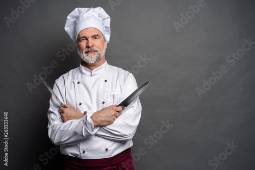 Fototapeta Portrait of a mature chef cook holding knifes isolated on a black background. obraz