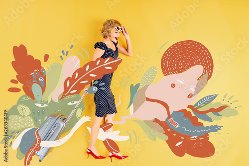 Fototapeta top view of young shocked elegant woman with suitcase lying on yellow background with floral illustration obraz na płótnie