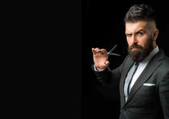 Confident barber at barbershop. Barber and hairdresser salon. Beard care, perfect beard. Bearded man in formal business suit. Brutal male hipster cut hair with hairdressing scissors - copy space