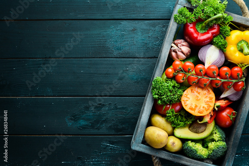 Fresh vegetables and fruits in a wooden box. Avocados, tomatoes, strawberries, melons, potatoes, paprika, citrus. Top view. Free space for your text.