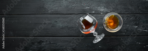 Fototapety, obrazy: A glass of brandy on a black background. Top view. Free space for your text.