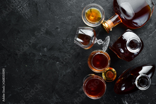Photo sur Toile Alcool A bottle of cognac and glasses on a black background. Brandy. Top view. Free space for your text.
