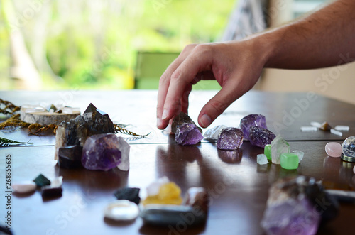 Beautiful Clear Quartz, variety of crystal on wood table. Bright Quartz crystal, healing crystal being held in hand. Woman holding quartz tower, crisp colors in natural lighting. Vibrant meditation.