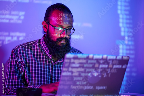 Fotografiet Serious bearded IT man in eyeglasses sitting at the table and using laptop compu