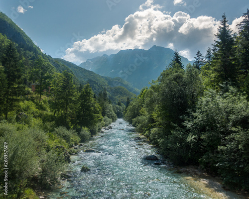 Isonzo river in slovenian julian alps with mountains in the background