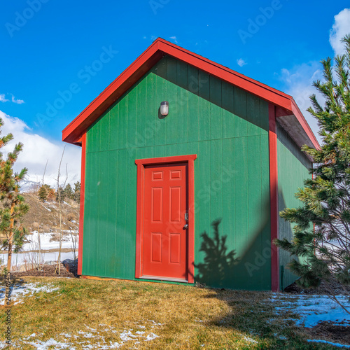 Fotografie, Tablou Clear Square Small storage shed on grassy terrain with trees and powdery snow