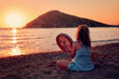 Female hippie sitting on the sands of a beach and playing bendir at sunset