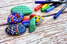 Hand-painted Colorful Pebble Stones And Acrylic Pens On A Vintage Textured Wooden Table. Stone Painting.