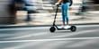Leinwanddruck Bild - Elektroroller fährt auf einer Straße durch die Stadt