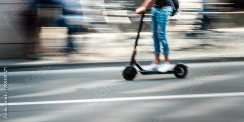Fotografiet  Elektroroller fährt auf einer Straße durch die Stadt
