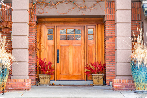Fotomural  Brown wooden front door with decorative glass panels at the entrance of a home