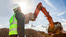 Construction Worker Or Engineer On Construction Site With Excavator