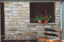 Wooden Table And Bench In Front Of Stone Wall