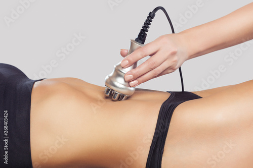 Obraz na plátne  The doctor does the Rf lifting procedure on the abdomen and hips of a woman in a beauty parlor