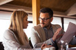 A handsome beard businessman explains to a beautiful colleague what to change in the report while sitting and drinking coffee.