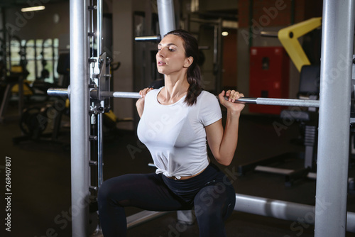 Foto Beautiful fitness young girl doing squats with the barbell in smith machine at the gym