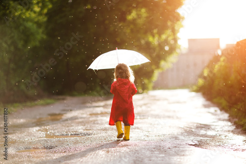 Photo  Happy child  with an umbrella playing out in the rain in the summer outdoors