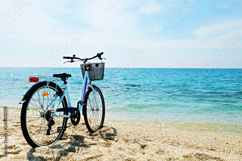Foto op Plexiglas Fiets Feminine bicycle of comfort class with empty basket on the sandy beach of mediterranean sea. Blue cruiser bike on sunny day at sea shore with a lot of copy space for text.