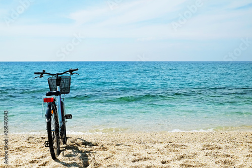 Foto op Plexiglas Feminine bicycle of comfort class with empty basket on the sandy beach of mediterranean sea. Blue cruiser bike on sunny day at sea shore with a lot of copy space for text.