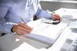 Leinwandbild Motiv Businessperson Calculating Invoice