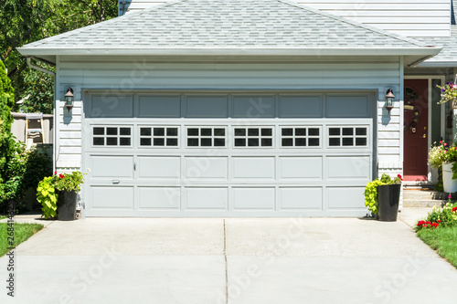 Fotografía  Wide garage door of residential house and concrete driveway in front