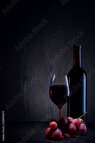 Foto auf Leinwand Wein Red wine in glass and bottle and bunch of grapes on wooden table