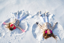Two Little Girl Making Snow Angel While Lying On Snow. Happy Girl On A Snow Angel Shows.