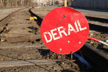 Red Derail Warning Symbol Sign On Old Abandoned Railroad Tracks