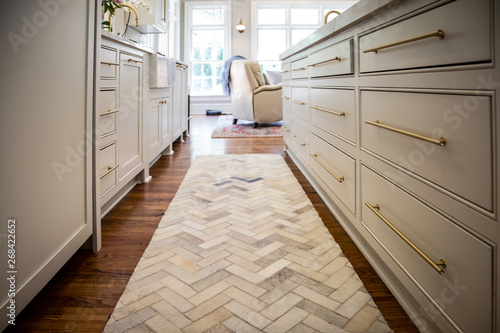 Photo Low view of new renovated kitchen cabinets with Herringbone Runner Rug