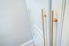 Wall Of Tall White Wood Painted Cabinets With Modern Gold Handles Hardware For Storage